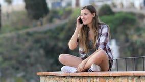 Tonårs- flicka som kallar på telefonen som sitter på en avsats