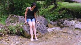 Tonårs- flicka som kopplar av med hennes fot i flodvatten lager videofilmer