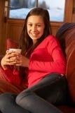 Tonårs- flicka som kopplar av på sofaen med den varma drinken Arkivbilder