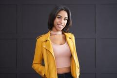 Tonårs- flicka som ler i gulingläderomslag arkivfoto