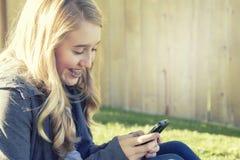 Tonårs- flicka som ler, medan genom att använda en mobiltelefon Arkivbilder