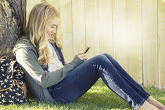 Tonårs- flicka som ler, medan genom att använda en mobiltelefon Arkivbild
