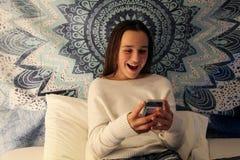 Tonårs- flicka som ler på hennes mobiltelefon, medan smsa royaltyfria bilder