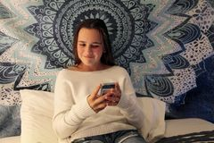 Tonårs- flicka som ler på hennes mobiltelefon, medan smsa arkivfoto