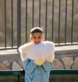 Tonårs- flicka som ler, slåget in i stor päls Arkivfoto