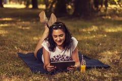 Tonårs- flicka som ligger på en filt i natur och använder en minnestavla Royaltyfri Bild