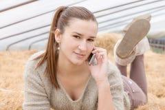 Tonårs- flicka som ligger på höstackar genom att använda en mobiltelefon Royaltyfria Bilder