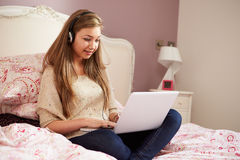 Tonårs- flicka som ligger på säng genom att använda bärande hörlurar för bärbar dator Royaltyfri Foto