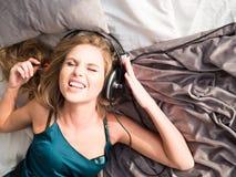 Tonårs- flicka som lyssnar till musiken på sängen Arkivbild