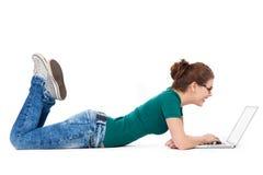 Tonårs- flicka som ner ligger med bärbara datorn Royaltyfri Fotografi