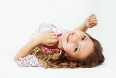 Tonårs- flicka som ner ligger, med smycken på hennes hals royaltyfria foton