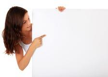 Tonårs- flicka som pekar på det blanka vita tecknet Arkivfoto