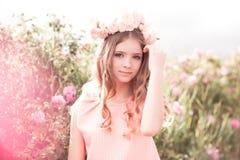 Tonårs- flicka som poserar i rosträdgård Royaltyfri Bild