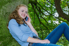 Tonårs- flicka som ringer mobilen i grönt träd Royaltyfria Foton