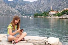 Tonårs- flicka som sitter nära havet och har gyckel med smart ph Arkivfoto