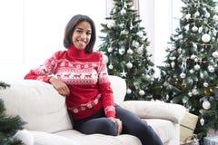 Tonårs- flicka som sitter på soffan bredvid julgranen arkivfoto