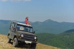 Tonårs- flicka som sitter på taket av en SUV i bergen royaltyfri foto