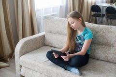 Tonårs- flicka som sitter soffan och ut ser minnestavlan Royaltyfria Foton