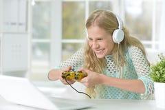 Tonårs- flicka som spelar en dataspel Arkivbild