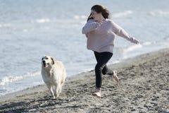 Tonårs- flicka som spelar med hennes hund på en strand royaltyfri bild