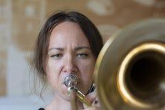 Tonårs- flicka som spelar trombonen arkivfoton