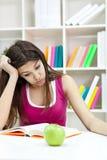 Tonårs- flicka som studerar på skrivbordet som tröttas Royaltyfri Fotografi