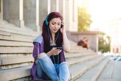 Tonårs- flicka som surfar det netto på smartphonen Arkivbilder