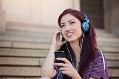 Tonårs- flicka som surfar det netto på smartphonen Arkivfoto