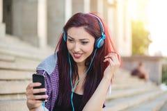 Tonårs- flicka som surfar det netto på smartphonen Fotografering för Bildbyråer