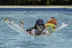Tonårs- flicka som svävar på en luftmadrass royaltyfria foton