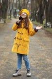 Tonårs- flicka som talar på hennes smartphone, medan det regnar arkivbilder