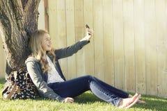 Tonårs- flicka som tar en selfie med en mobiltelefon Royaltyfria Bilder
