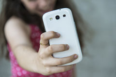 Tonårs- flicka som tar en selfie med hennes telefon royaltyfri bild