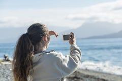 Tonårs- flicka som tar en selfie med hennes telefon i Alaska royaltyfri bild