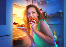 Tonårs- flicka som tar mat från kylskåpet på natten Arkivbilder