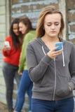 Tonårs- flicka som trakasseras av textmeddelandet royaltyfria foton