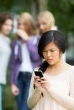 Tonårs- flicka som trakasseras av textmeddelandet på mobiltelefonen Arkivfoton