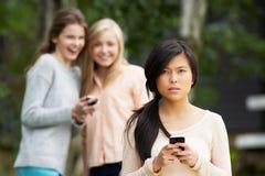 Tonårs- flicka som trakasseras av textmeddelandet på mobiltelefonen royaltyfria foton