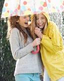 Tonårs- flicka som två beskyddar från regn under paraplyet Royaltyfria Bilder