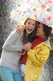 Tonårs- flicka som två beskyddar från regn under paraplyet Fotografering för Bildbyråer