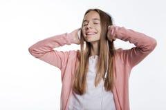 Tonårs- flicka som tycker om favorit- sånger i hörlurar arkivbild
