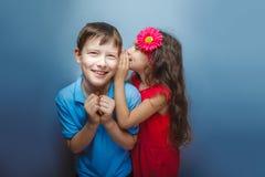 Tonårs- flicka som viskar i örat av tonåriga pojkar på Royaltyfri Foto
