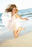 Tonårs- flickabanhoppning i luft på strandferie Arkivbilder