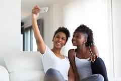 Tonårs- flickor för afrikansk amerikan som tar en selfiebild med en sm fotografering för bildbyråer