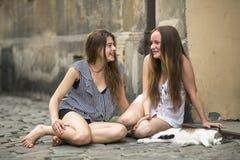 Tonårs- flickor för flickvänner som sitter på trottoaren med en katt Fotografering för Bildbyråer
