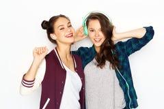 Tonårs- flickor i hörlurar som lyssnar till musik royaltyfri bild