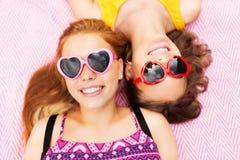 Tonårs- flickor i solglasögon på picknickfilten Arkivbilder