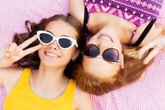 Tonårs- flickor i solglasögon som visar fredtecknet Arkivbild
