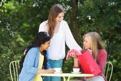 Tonårs- flickor med shoppingpåsar på det utomhus- kafét fotografering för bildbyråer