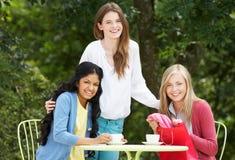 Tonårs- flickor med shoppingpåsar på det utomhus- kafét arkivfoto